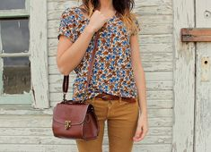 Floral shirt, mustard jeans, tan bag.