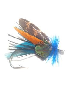 Hand tied fly fishing boutonniere  Style: Brook Trout  Colors: Brown, tan, orange, teal, emerald green  Size: 2 Tall, 3 Wide  Materials: Feathers  Brooch style pin for easy wear  Custom designs available.  Email BlueSpruceFlyCo@Hotmail.com