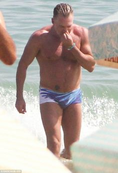 Muscular: The TV star shows off his incredible physique as he emerges from the sea