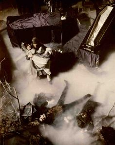 High-angle shot of Roger Davis as Jeff Clark carrying Kathryn Leigh Scott as Maggie Evans away from altar; with Jonathan Frid as Barnabas Collins and John Karlen as Willie Loomis, both dead on floor; fog surrounding them and coffin in upper right corner.