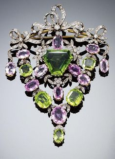 Circa 1900 peridot, pink topaz, and diamond brooch/pendant. The central swing pendant designed as a garland composed of rose- and circular-cut diamonds and oval pink topaz, centering on a modified triangular-shaped peridot, within a frame set with graduat Edwardian Jewelry, Antique Jewelry, Vintage Jewelry, Edwardian Era, I Love Jewelry, Fine Jewelry, Jewelry Design, Suffragette Jewellery, Saphir Rose
