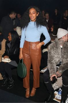 Solange Knowles wears a blue sweater, leather pants, Mary Jane heels, and a top-handle Mansur Gavriel bag