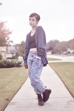 Spiked choker, black tank top, blue cardigan, high-waisted acid-wash jeans, black Dr. Martens boots