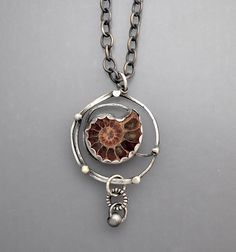 A sterling silver necklace with a ammonite fossil in a unique spiral setting on a substantial heavy gauge chain. Very nice !! The chain length is 19 and the pendant drop is 2- 1/4.