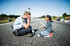 A young refugee girl plays with a police officer on a closed highway during a break. The refugees were trying to march across Denmark to get to Sweden and were escorted by the police that tried to convince the refugees to cancel their march. Photo credits: Michael Drost-Hansen.