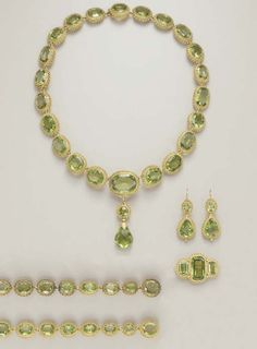 AN ANTIQUE PERIDOT PARURE c1820s Comprising a necklace, suspending a detachable briolette-cut peridot pendant, by a gold foliate cap, to the circular-cut peridot surmount, from a series of oval and cushion-cut peridots, each within a gold beaded frame; a brooch, two bracelets and pair of ear pendants en suite, mounted in gold