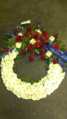 We Love You funeral wreath. White carnations, red and white roses. americasflorist.com