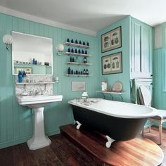 Muted turquoise beadboard complement the warm-hued wood floor and brown paint on the bath's exterior. A smattering of cobalt blue bottles and marble shelves and a backsplash for the sink punch up the look while keeping it spare.