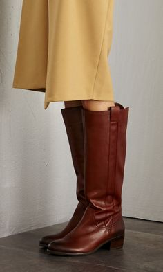 Tried and true classic: A genuine leather riding boot with a back zipper, pull tabs and a stacked heel.