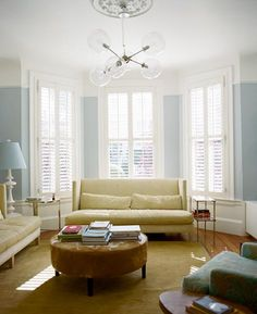A gorgeous (palladium blue?) living room. With the super wide white crown molding and base boards. It even has all three windows fully trimmed out with great molding.