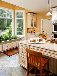 White cabinetry pops against the yellow wall color in this bright kitchen and creates a convenient sitting area at the center island. A container garden sits under the bay windows, which provide plenty of natural light for the plants.