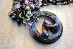 Recycled art glass that has been flame-worked and hand sculpted. Amethyst beads and glass teardrops dangle below a glossy gunmetal chain, clustered above a striking art glass disc in swirling shades of purple and blue with hints of green.