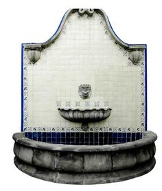 Spanish style wall mount stone fountain is decorated with talavera tiles. Both the cantera stone fountain ornaments and the tiles were handcrafted in Mexico. by Rustica House