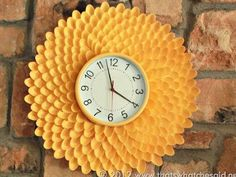Use plastic spoons, spray paint, and a cheap clock to create a colorful and creative wall hanging.