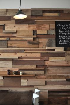 Slowpoke Espresso, Melbourne, Australia, designed by Anne-Sophie Poirier. The 12-meter-long feature wall was created using timber offcuts from local furniture makers. The result is a textured wall showcasing a variety of timber species and colors. Some wider blocks protrude from the wall to create shelves for condiments above each table.