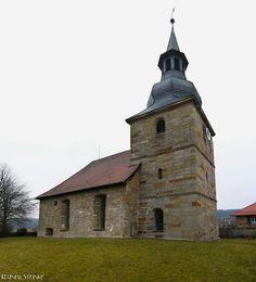 Wehrkirche mit Zackenportal in Bronn bei Pegnitz (Fränkische Schweiz).  Der Name Bronn kommt von Brunnen der Ort Bronn wird erstmals im Jahr 1196 urkundlich erwähnt.  In einer alten Sage heisst es dass sich eine Katharina im Veldensteiner Forst verlaufen und an dieser Stelle aus dem Dickicht herausgefunden habe. Als erstes hat sie sich am Bronner Quellwasser erfrischt. Zum Dank für die Rettung ließ sie hier eine Kapelle für ihre Namenspatronin die heilige Katharina bauen.  Während der…