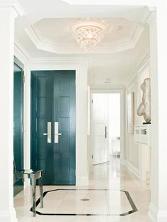 Chic foyer features octagon tray ceiling punctuated with Robert Abbey Bling Chandelier over black and white octagon floor which mimics the tray ceiling.