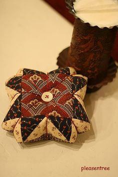 Civil war fabrics in a block and made into a pincushion.