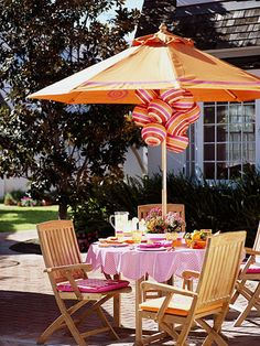 Add pizzazz to a teak outdoor dining set with a colorful umbrella, paper lanterns, and pretty paint swirls and stripes (from Better Homes and Gardens)