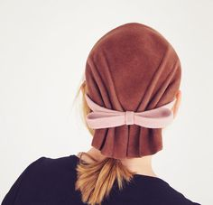 The detail on this hat is mainly in back, with a gathering of the material into what looks like a gathered scarf with a bow. The wit of this is unmistakable! The front has a band which sits like a headband, across the center of the crown. The material of the hat is fine wool velour felt. The two colors are brown and beige. The brown is between cocoa and mushroom, not quite as reddish brown as some of the photos appear. There is an inner grosgrain ribbon. The label is from Spokanes The…