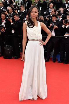 Zoe Saldana con  un vestido blanco con falda y detalles plisados y un robusto cinturón de cadena de Victoria Beckham.