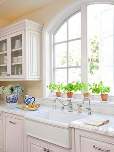 ✥ Windows. Traditional White Kitchen. Classic Charm. In keeping with the goal of blending elegance and comfort, the formal look of the cabinetry is balanced by its soft white color and slightly distressed finish. Glass fronts on some upper cabinets further lighten the look. Here, the apron-front main sink conveys vintage farmhouse charm amid the traditional elegance of marble countertops.