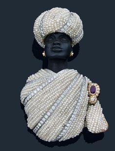 Codognato.Important clip «Maure» en or jaune et gris entièrement drapé d'un habit de petites perles rehaussé de lignes de diamants de taille brillant. Agrafe sertie d'un rubis dans un entourage de brillants. Coiffé d'un turban de petites perles et diamants de taille brillant orné d'une perle mabe.Photo Antoine Aguttes