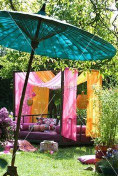 modernes tagesbett mit baldachin aus pink und orangefarbenen tchern im sonnigen garten asiatischer bambusschirm im - Modernes Tagesbettgestell