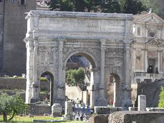 The Arch of Septimius Severus in the Forum Romanum in Rome, Italy. The inscription is catalogued as CIL VI 1033 (cf. VI 36881). Behind the arch to the right is the church of San Giuseppe dei Falegnami with Carcere Mamertino at ground level. Behind to the left is the Tabularium.