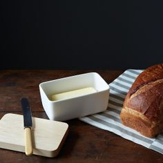 Store your butter beautifully with this porcelain dish.  Get it here: http://food52.com/provisions/products/380-modern-white-porcelain-butter-dish-with-maple-lid. #F52Provisions