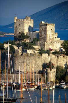 Crusader castle in Bodrum harbor, Turkey/ views are stunning. Bodrum Kalesi was built by the Knights Hospitaller starting in 1402 as the Castle of St. Peter or Petronium. The construction of the castle began in 1402 under the German knight-architect Heinrich Schlegelholt. Construction workers were guaranteed a reservation in Heaven by a papal decree of 1409. They used squared green volcanic stone, marble columns and reliefs from the nearby Mausoleum of Maussollos to fortify the castle.