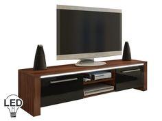 Klasický TV stolík s klasickým dizajnom. No opak je pravdou. Svoju jedinečnosť ukáže až po zotmení. Po celej dĺžke hornej dosky sa nachádza voliteľné LED osvetlenie, ktoré vyzerá super a dodá nábytku a miestnosti úžasný efekt. V strednej časti sa nachádza praktický priestor na umiestnenie audio/video techniky. Podlhovasté úchyty pôsobia elegantne. Farebné prevedenie je slivka v kombinácii s čiernou vo vysokom lesku.