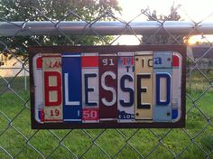 OOAK Blessed license plate sign constructed out of reclaimed license plates from various states. Mounted on a dark stained piece of wood then sealed