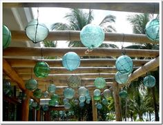 Hanging glass fishing floats in ocean blues and sea greens, would look beautiful with white for coastal vintage style