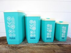 A lovely set of vintage plastic turquoise canisters with white flowers..