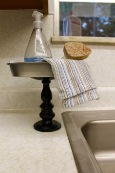 Use a cake pan from the dollar store and a candlestick to make an organizer next to your sink to keep everything clean and organized. I love dollar store crafts!