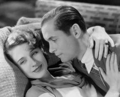 Medium shot of Norma Shearer as Amanda and Robert Montgomery as Elyot hugging or embracing on a couch or sofa. TBS, Inc.