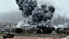 Smoke rises after an air strike on an Islamic State position in the Syrian town of Kobane (12 October 2014)