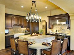 Tuscan Kitchen: A tiered island provides a preparation area as well as a dining area. From HGTVRemodels.com