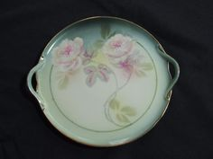 Beautiful antique plate in sea green mist colored background with pastel pink white roses. The long stems flow. There are two handles. This is a perfect size for serving sweet treats at your special dinner table.RS Germany green mark was introd...