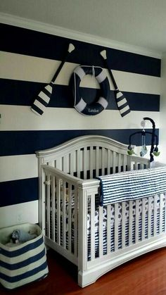 Love the oars and lifesaver above the crib against the striped wall.