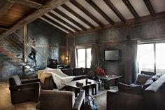 Salon chalet moderne et luxe. Canapé en cuire. Escalier métal. Parquet en bois. Peinture béton et métal. Décoration d'intérieur cosy et haut de gamme.