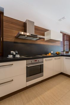 Small kitchen in modern home with white cabinets and black backsplash