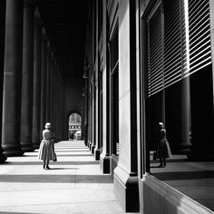 A woman with a dress and a hat walking down a portico in the city. Undated, Chicago, IL