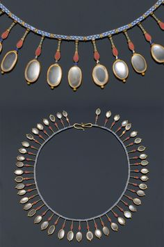 An Archaeological Revival Enamel and Moonstone Fringe Necklace by Carlo Giuliano. Blue enamelled tubes suspend drops enamelled in green, red and blue, each terminal features a cabochon moonstone. ca. 1874-1895.
