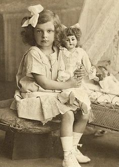 Sweet vintage photograph of a young girl with her doll, circa 1920.