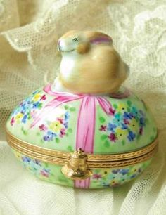"""Authentic Limoges Bunnykin's Nest Egg    A glass carrot hides within a coveted provençal box as a contented cottontail perches atop. Hand painted in the sleepy French town where the dainty collectibles have been created for centuries. 2""""."""