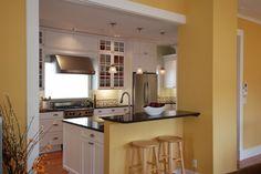 Yellow walls, white cabinets, black countertops
