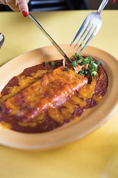 The signature enchiladas of El Coyote in West Hollywood, California, are filled with sauted sweet onion and drowned in an earthy, spicy sauce.