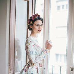 Look perfecto para una boda de invierno: vestido de manga larga y falda de vuelo, con corona floral en el pelo.